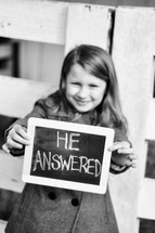 "A young girl holds out a chalk board on which is written, ""He answered."""