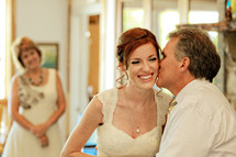 father kissing his daughter bride before a wedding