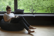 a woman sitting in a beanbag reading a Bible