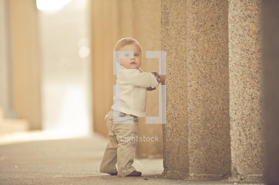toddler walking up to a pillar