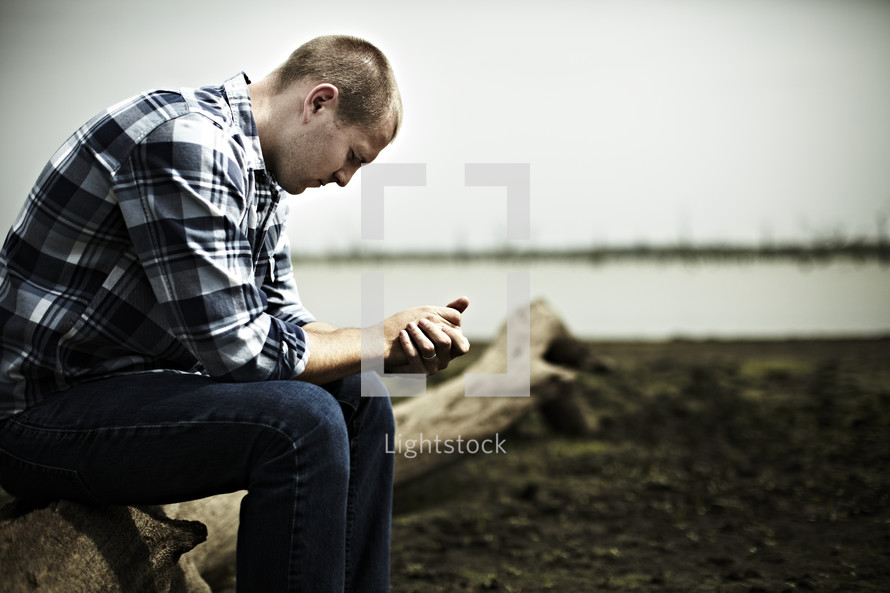 A young man prays on a log next to a lake bed.
