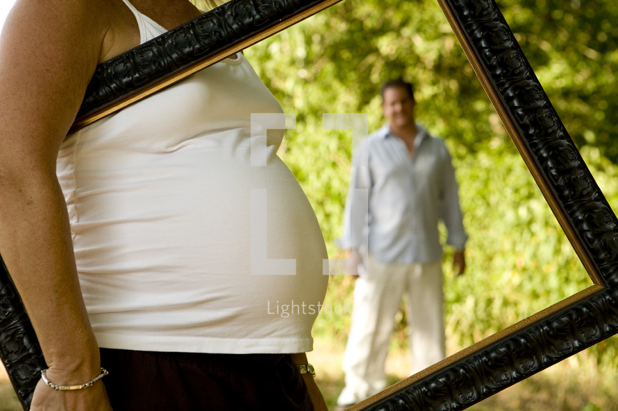 pregnant belly and father behind a frame carried by mother