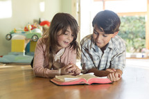 Brother and sister reading Bible together