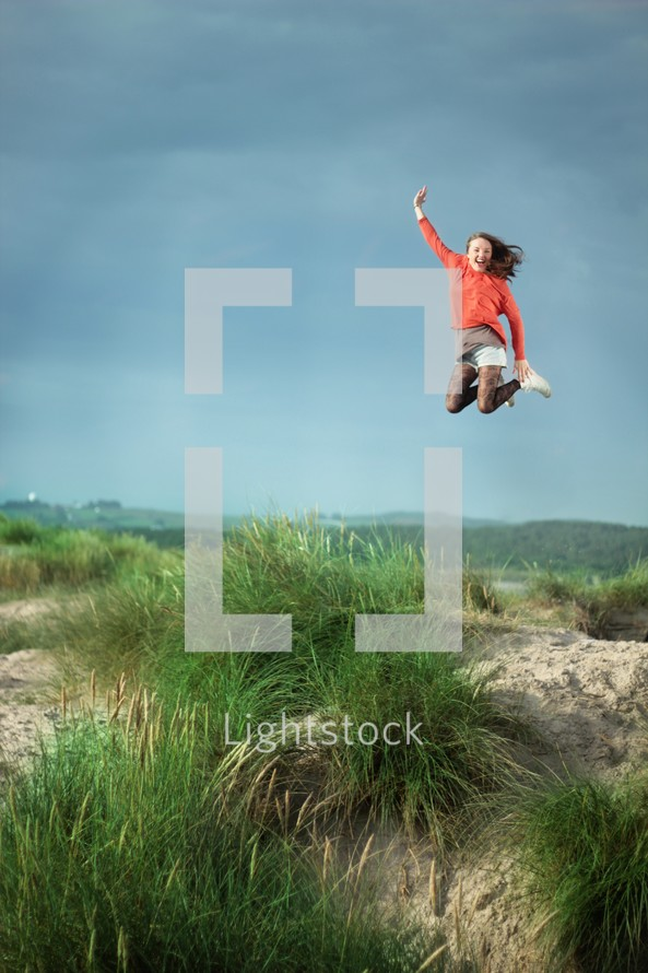 teen girl jumping for joy in a field