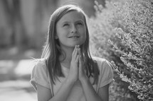 a child praying outdoors looking up to God