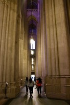 women walking beside tall columns in a cathedral