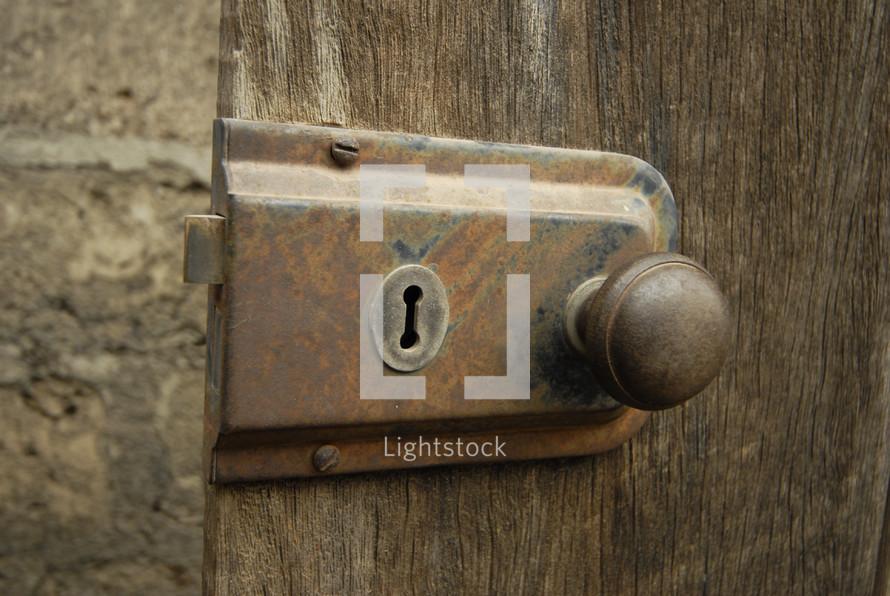 A rusty doorknob and lock on an old wooden door.