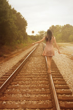 woman walking down railroad tracks