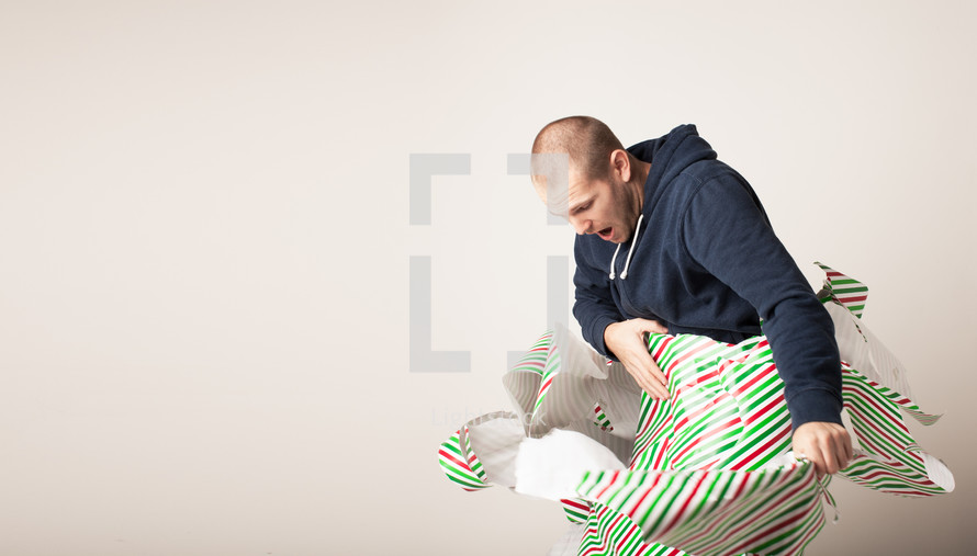 A man breaking free from Christmas wrapping paper