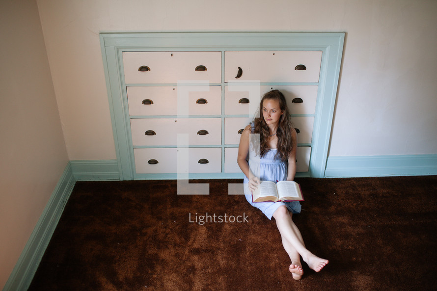 woman reading a bible sitting on the floor in front of a dresser