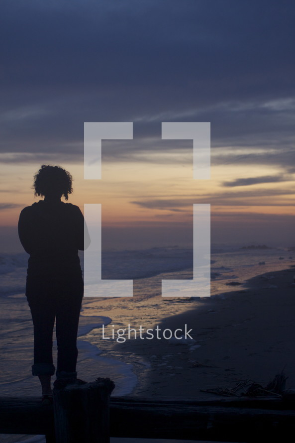 closeup of a woman standing on a pier in front of the ocean