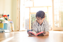 boy reading bible lying on floor