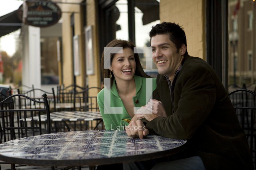 man and woman sitting at a cafe table