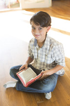 A boy sitting on the floor and reading the Bible.