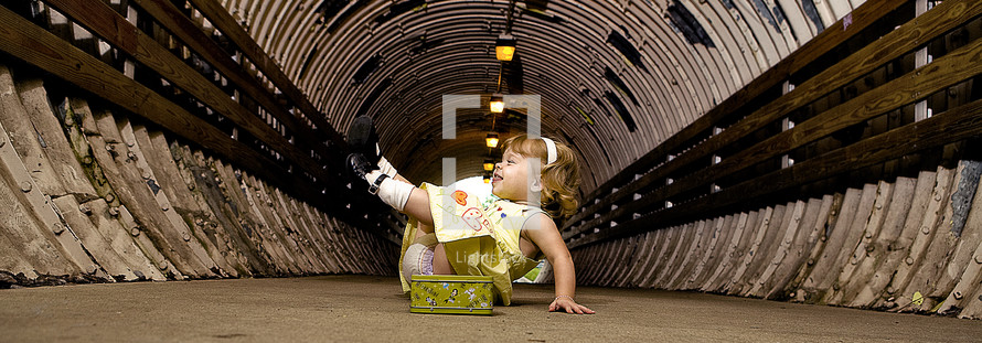 silly toddler girl playing in a tunnel