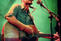 musician on stage playing a guitar and harmonica