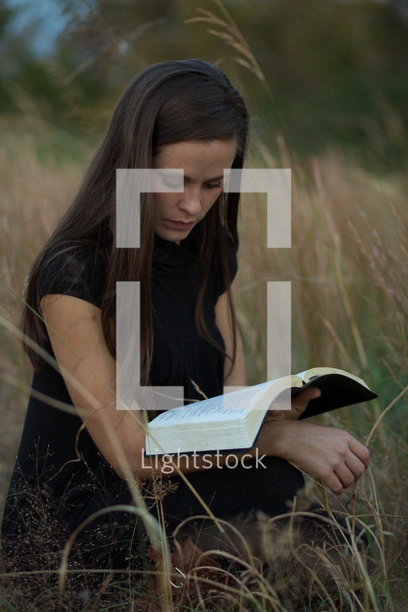close up of woman reading a Bible in a field