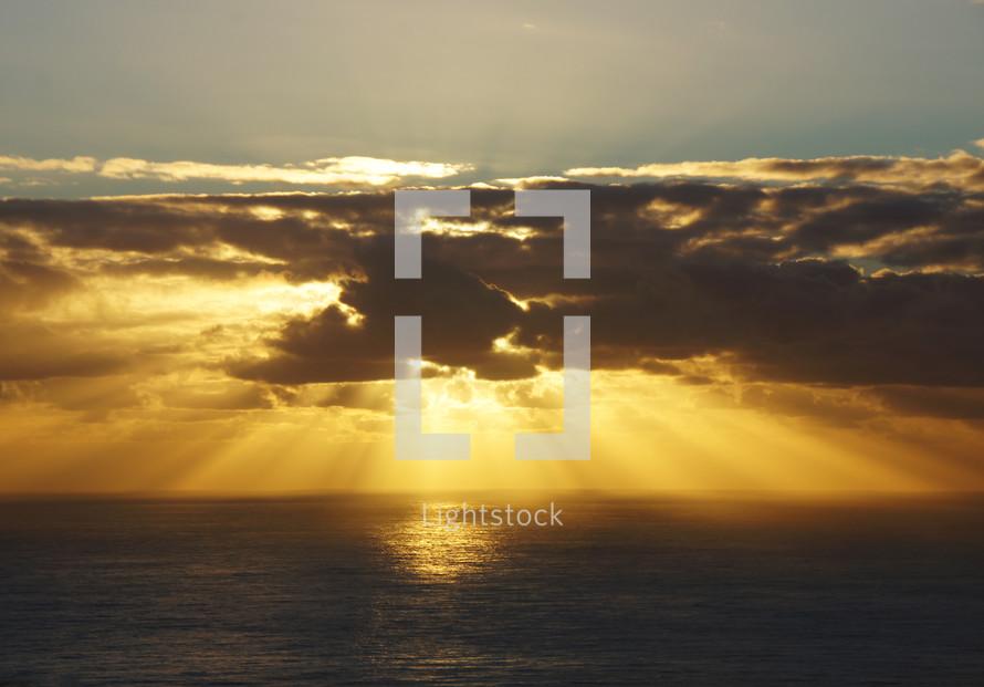 Sun rays over the ocean through dark clouds