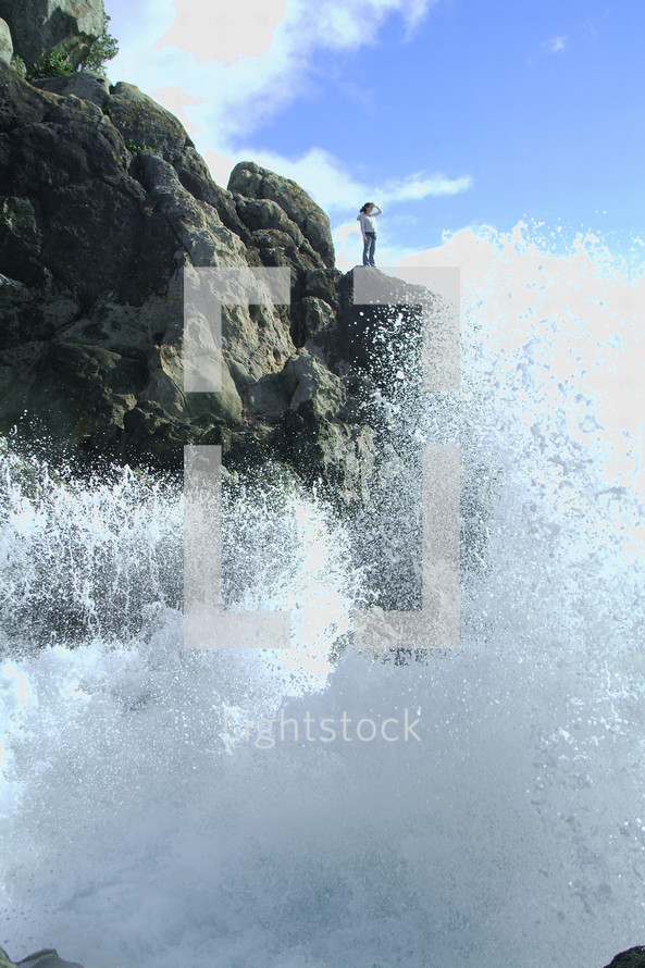A woman looking out at waves crashing against a rocky shore.