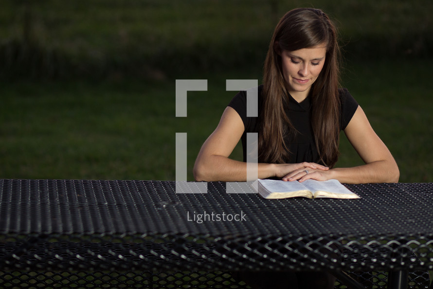woman sitting at a picnic table reading a Bible