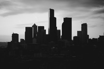 Silhouette of city skyline on hazy day.
