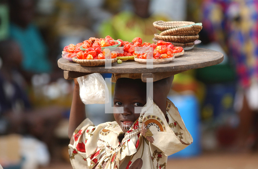 African child carrying a tray of tomatoes on her head in the local market