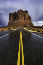 Rain clouds wet the road that winds through Arches National Park in Moab Utah