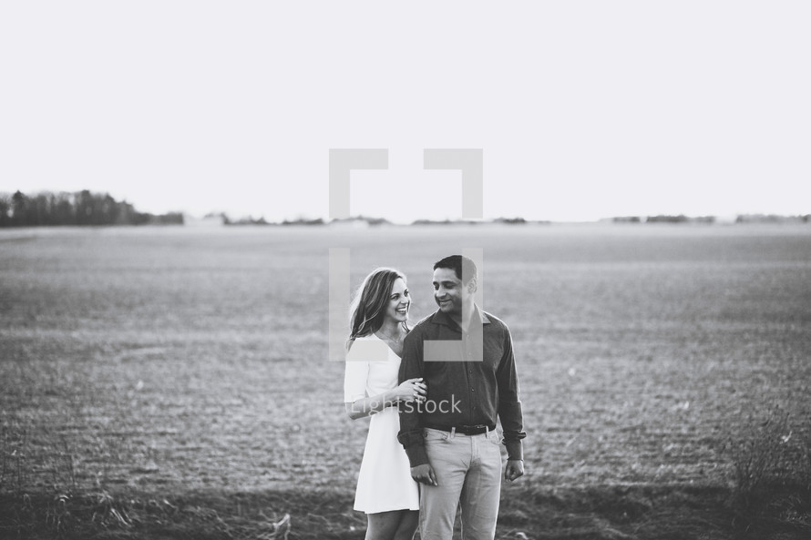a couple embracing standing in a field