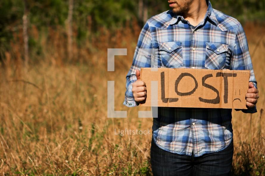 "Man holding ""Lost"" cardboard sign"