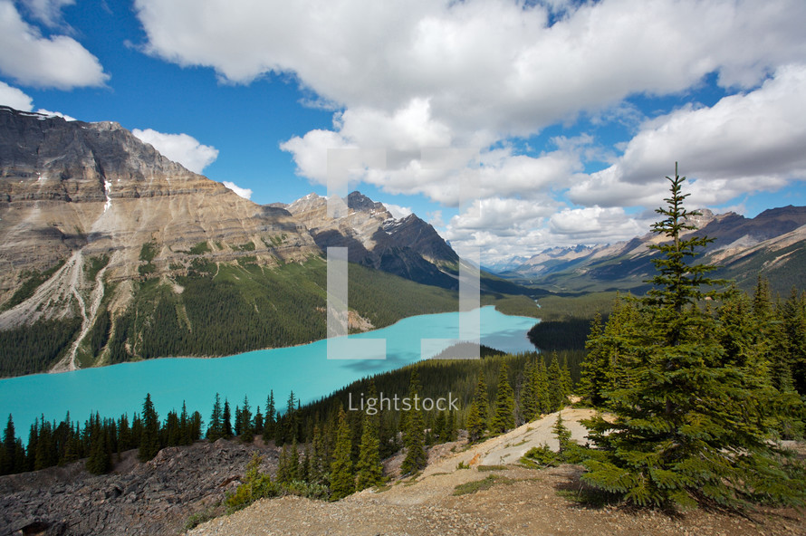 Lake running through rocky mountains with clouded sky
