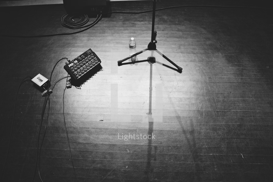 empty stage with guitar pedals and microphone stand