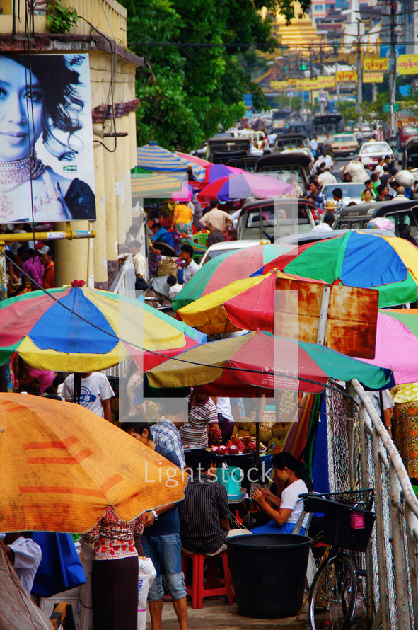 Colored umbrellas on a busy sidewalk during market day