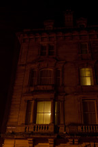 lights on in the windows of a city townhouse