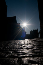Stone cobbles along a side street bank looking towards a cathedral in the distance with the sun beaming through