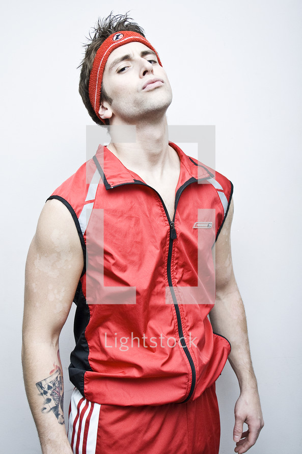 Kevin Fitness; man in red workout wear; red headband, vest, shorts.
