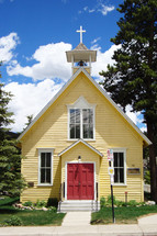 Small yellow church with red doors