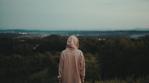 a woman in a hoodie looking out at mountains