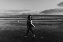 a woman bundled up walking on a beach shore