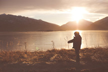 boy child in a coat standing by a lake under sunlight