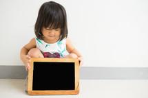 a little girl holding a chalkboard