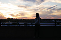 a silhouette of a girl at sunset