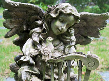 A statue of an Angel and a bird fellowship together at a pet cemetery reminding us that death is not the end or final chapter but a passing from this life to the eternal life where there is no more death, no more crying, no more sickness and no more pain.