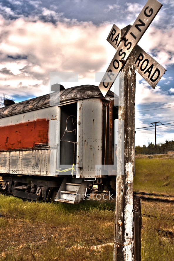 A railroad crossing sign in front of a train