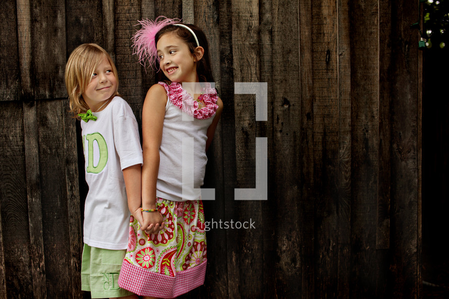 Two young girls holding hands by a wooden fence.