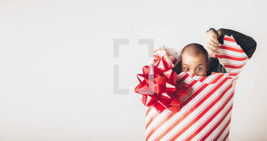 A man breaking free from wrapping paper