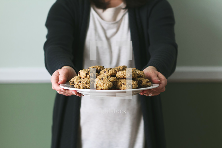 a woman presenting a plate of cookies
