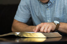 a man pointing to scripture while reading a Bible