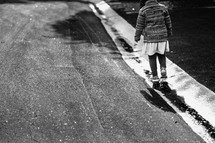a little girl walking in puddles along the curb
