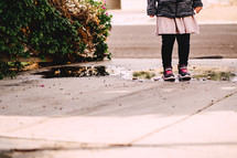 a little girl standing in a puddle