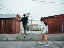 man and woman walking in a parking lot